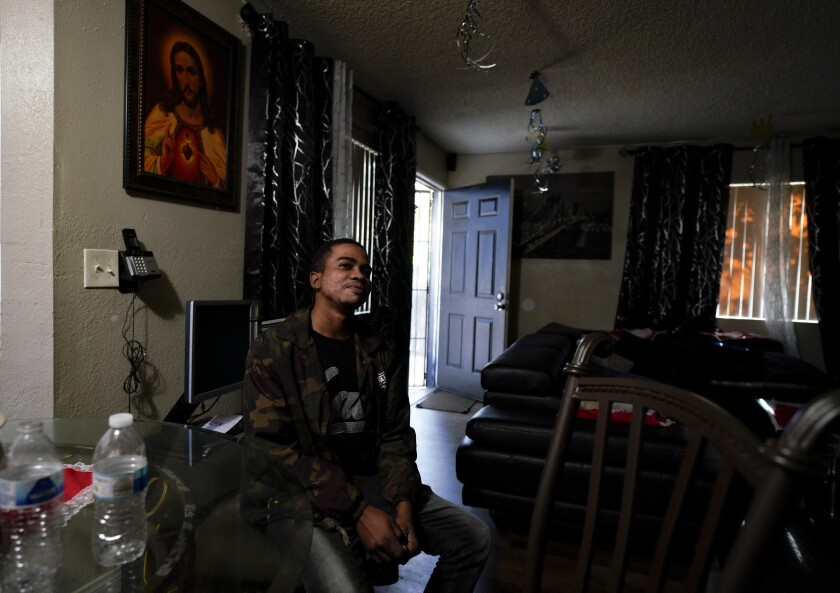 Patrick, 20, a refugee from the Democratic Republic of Congo, sits in his friend's apartment in Oak Park.