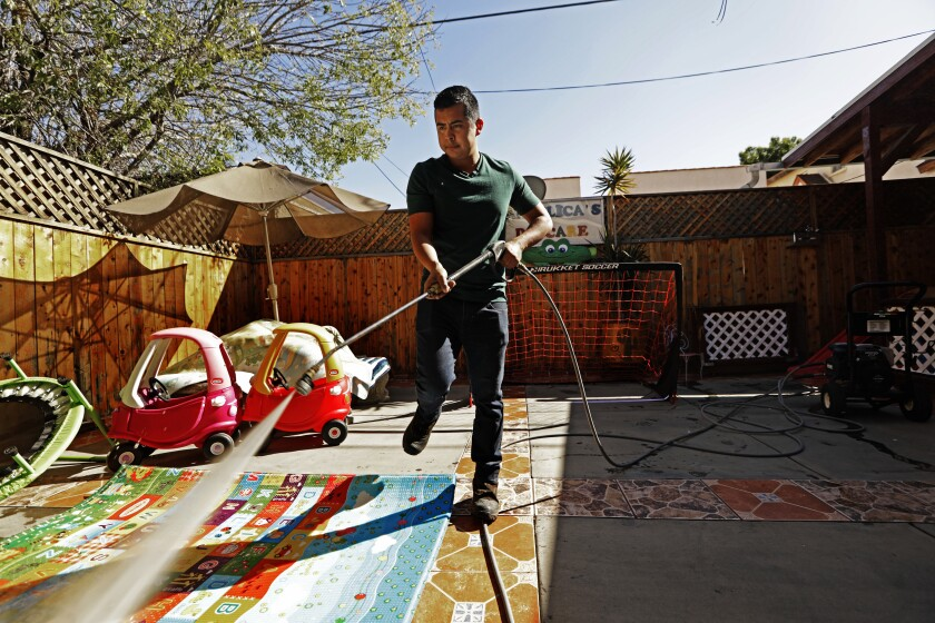 Luis Garcia spray-washes the children's equipment at Angelica's Daycare in Hollywood.
