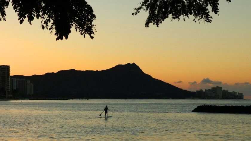 A solitary paddleboarder enjoying the sunrise view of Waikiki and Diamond Head. Doug Hansen photo