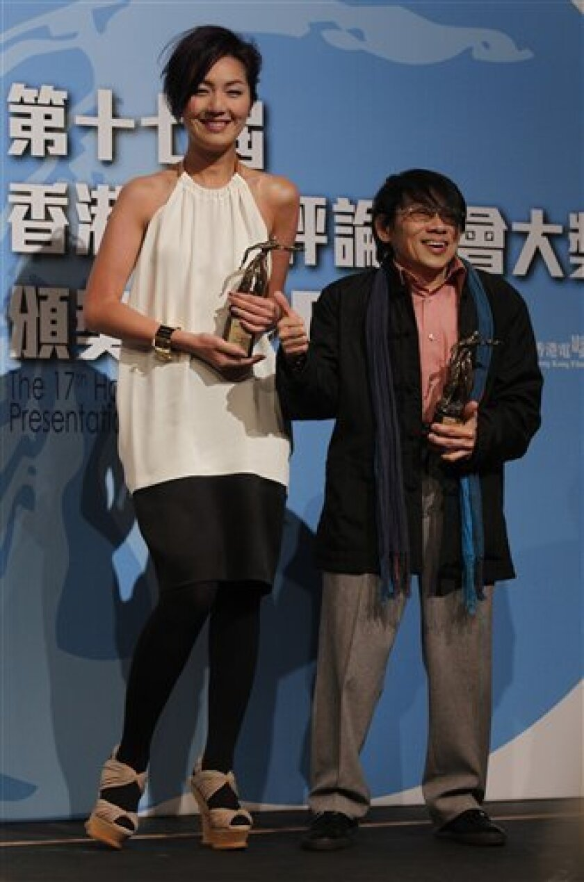 """Hong Kong actress Miriam Yeung and actor Teddy Robin hold their trophies after being awarded the Best Actress in the movie """"Perfect Wedding"""" and the Best actor in the movie """"Gallants,"""" respectively, during the Hong Kong Film Critics Society Awards presentation in Hong Kong Tuesday, Feb. 22, 2011."""