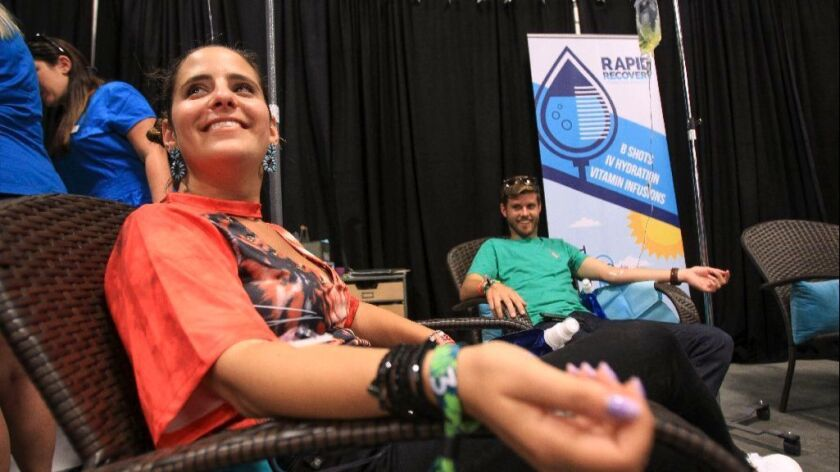 KAABOO attendee Spencer Berman, left, takes an IV containing a $100 vitamin mixture for energy calle