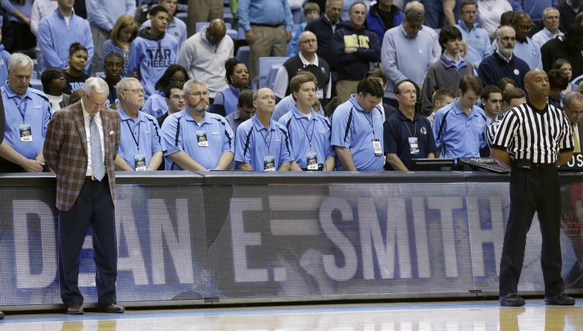 North Carolina coach Roy Williams and others in attendance observe a moment of silence for former coach Dean Smith who passed away recently, prior to an NCAA college basketball game against Georgia Tech in Chapel Hill, N.C., Saturday, Feb. 21, 2015. (AP Photo/Gerry Broome)