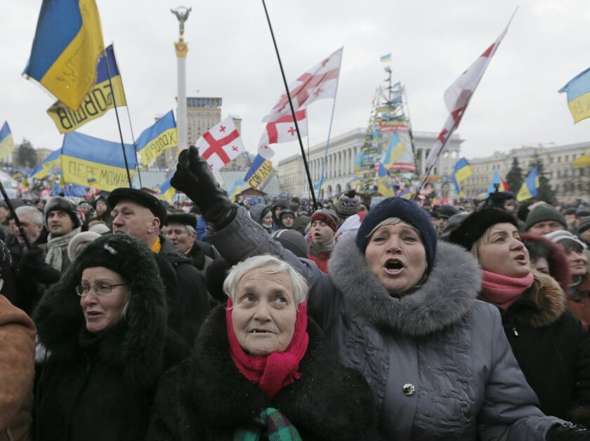 Pro-European Union activists shout slogans during a rally in the Independence Square in Kiev, Ukraine, Saturday, Dec. 7, 2013. As thousands of anti-government protesters kept their vigil in Ukraine's capital Saturday, officials sought to reduce their anger with assurances that Russian and Ukrainian presidents didn't discuss Ukraine joining a Russian-led customs union at a meeting this week. (AP Photo/Efrem Lukatsky)