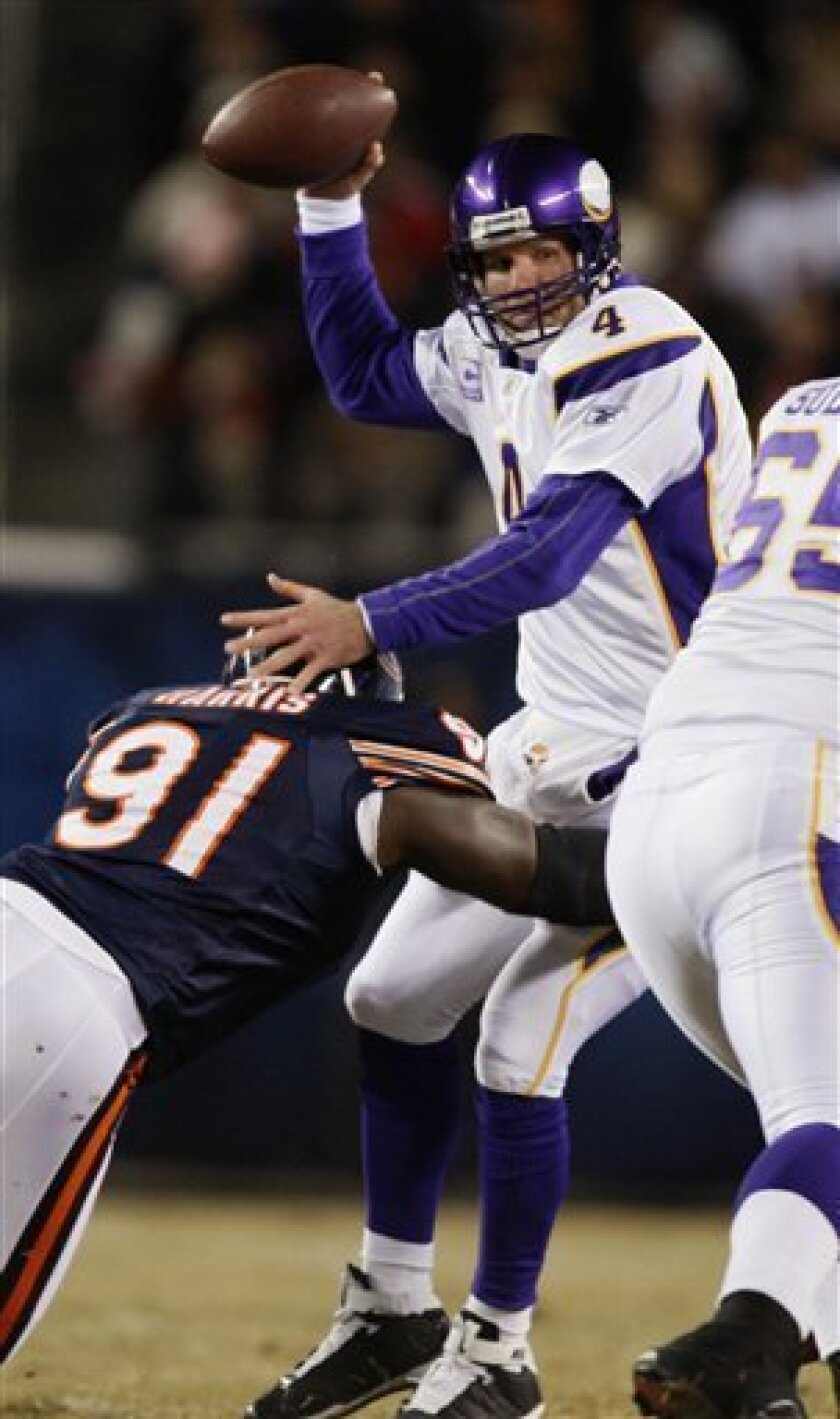 Minnesota Vikings quarterback Brett Favre (4) is sacked by Chicago Bears defensive tackle Tommie Harris (91) in the first quarter of an NFL football game in Chicago, Monday, Dec. 28, 2009. (AP Photo/Kiichiro Sato)
