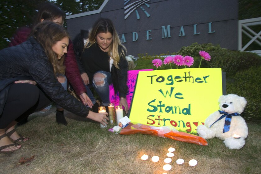 Ariel Pantoja, 19, left, Bayley Morrow, 18 and Makayla Bentley, 18, light candles at a makeshift memorial outside the Cascade Mall on Sept. 24, 2016, in Burlington, Wash.