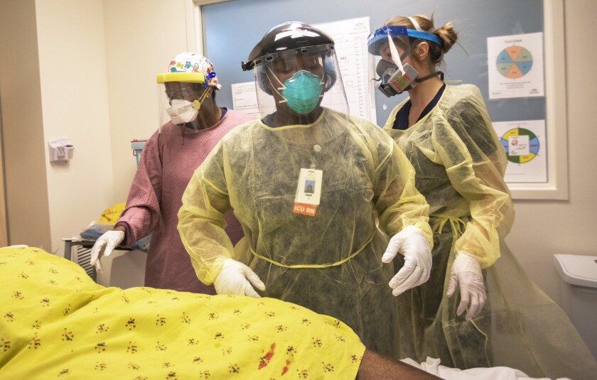 Nurses work at Martin Luther King Jr. Community Hospital as a patient was brought from the COVID-19 unit into the ICU.