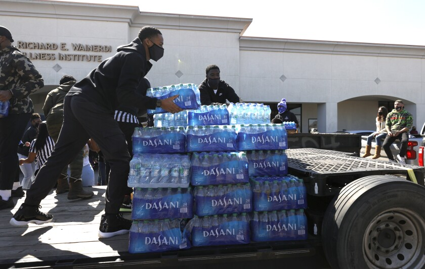 Volunteers stack cases of water during a water distribution event