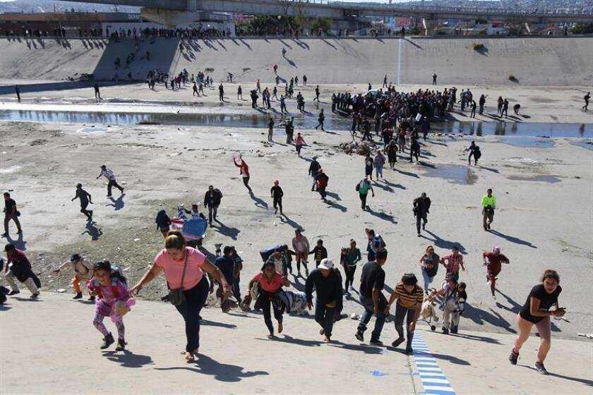 Dozens of people try to illegally cross from Mexico into the US at the El Chaparral border crossing point in Tijuana, Mexico, on Nov. 25, 2018. US border police fired tear gas at the migrants, causing them to withdraw and none were able to set foot on US soil. EFE-EPA/David Guzman