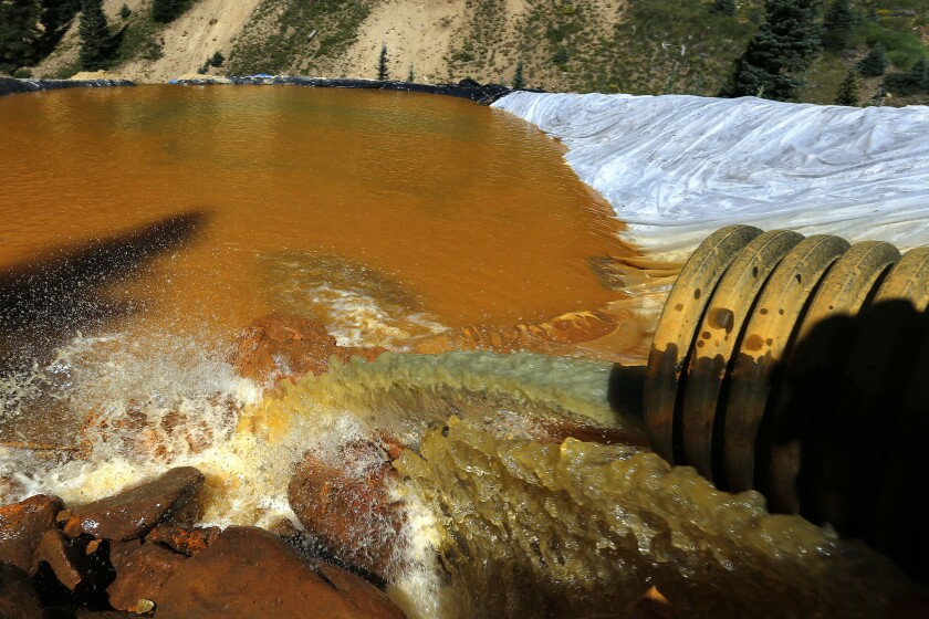 FILE - In this Aug. 14, 2015, file photo, water flows through a series of sediment retention ponds built to reduce heavy metal and chemical contaminants from the Gold King Mine wastewater accident, in the spillway downstream from the mine, outside Silverton, Colo. The owner of an inactive southwestern Colorado mine that was the source of a disastrous 2015 spill that fouled rivers in three Western states has filed a lawsuit seeking nearly $3.8 million in compensation for the federal government's use of his land in its ongoing cleanup response. (AP Photo/Brennan Linsley, File)