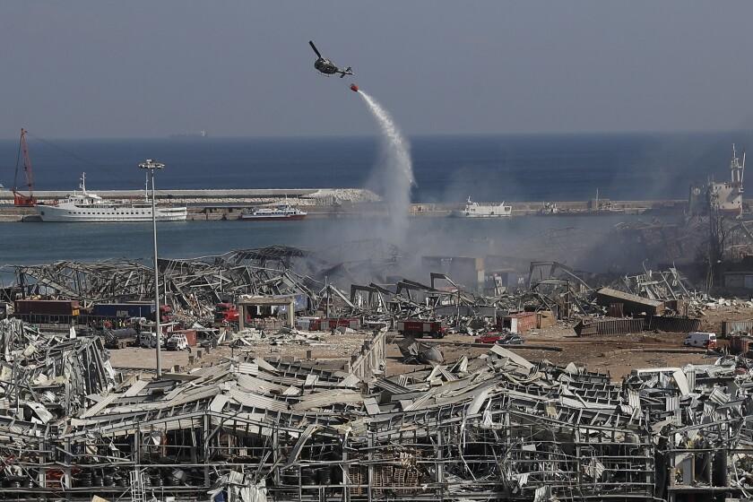 Un helicóptero del ejercito libanés arroja agua sobre el sitio de una explosión en el puerto de Beirut