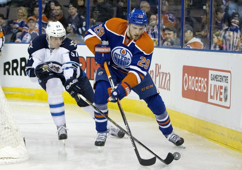 Winnipeg Jets' Tyler Myers (57) chases Edmonton Oilers' Leon Draisaitl (29) during the second period of an NHL hockey game Saturday, Feb. 13, 2016, in Edmonton, Alberta. (Jason Franson/The Canadian Press via AP)