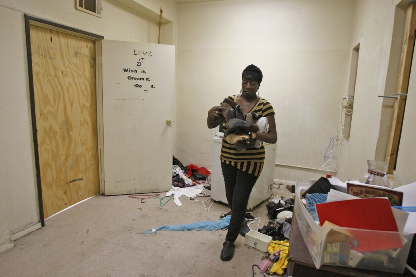 Patricia McDowell, 57, cleans up a storage area connected to her apartment in what was once office space that was converted into apartments at 5700 S. Hoover St. in Los Angeles. McDowell and her neighbors were told on short notice that they must vacate the building because of safety hazards.