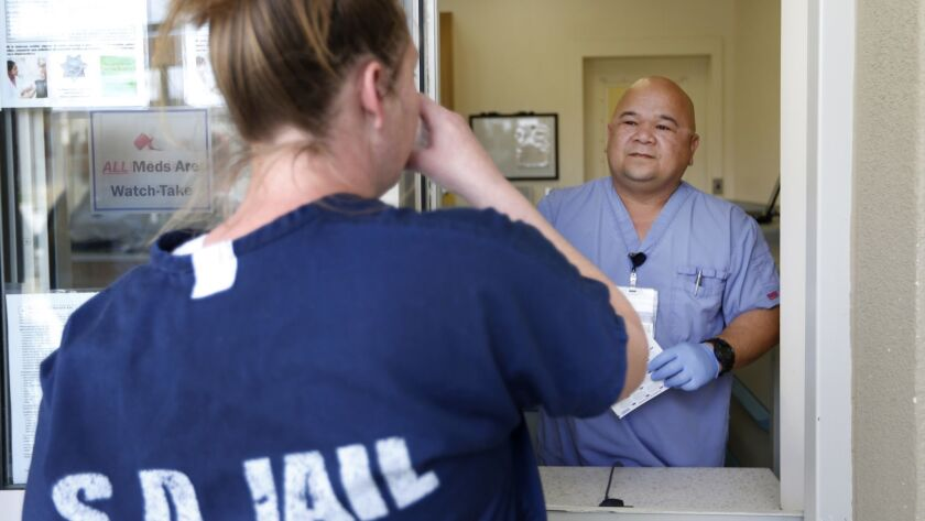 Ted Estacio watches an inmate take her medicine at the Las Colinas Detention and Reentry Facility.