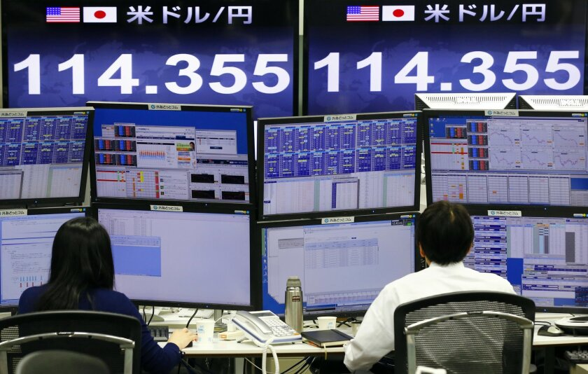 Money traders work in front of the computer terminal at a foreign exchange brokerage in Tokyo, Tuesday, Feb. 9, 2016. Asian markets tumbled Tuesday as renewed jitters about the global economy set off a wave of selling in banking stocks. The dollar fell to 114.90 yen from 115.58 yen. (AP Photo/Shizu