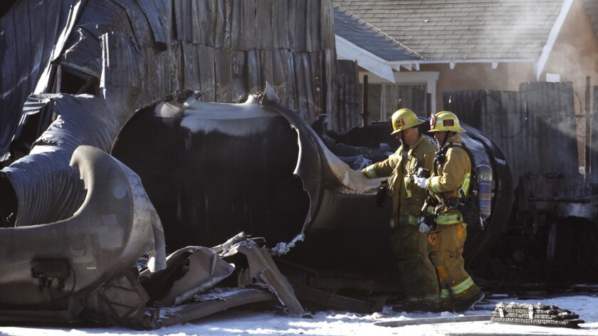 Firefighters look over a tank that exploded in the 200 block of West Slauson Avenue on Sunday morning. A tanker in a yard exploded, causing a fire to a nearby home and injuring two occupants.