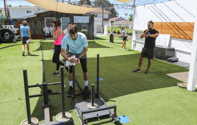 People are shown working out outdoors at The Movement Warehouse gym in Pacific Beach.