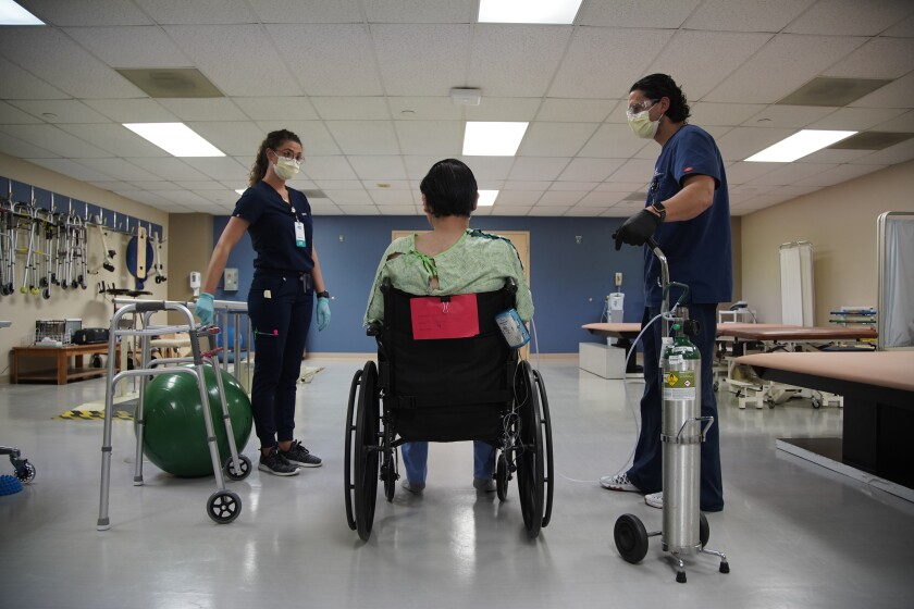 A COVID-19 patient rests in the wheel chair at Select Specialty Hospital
