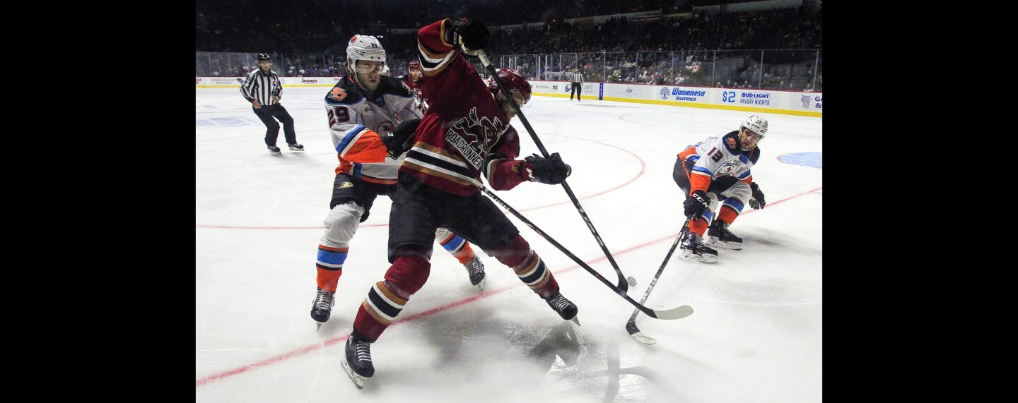The Gulls' Pontus Aberg, left, and Giovanni Fiore try to get the puck away from the Roadrunners' Dakota Mermis during the first period.
