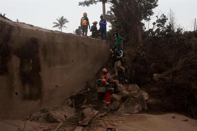 Bomberos evacúan a periodistas y voluntarios del Caserío San Miguel Los Lotes, en Escuintla (Guatemala) hoy, lunes 4 de junio de 2018, después de la erupción del volcán de Fuego. EFE