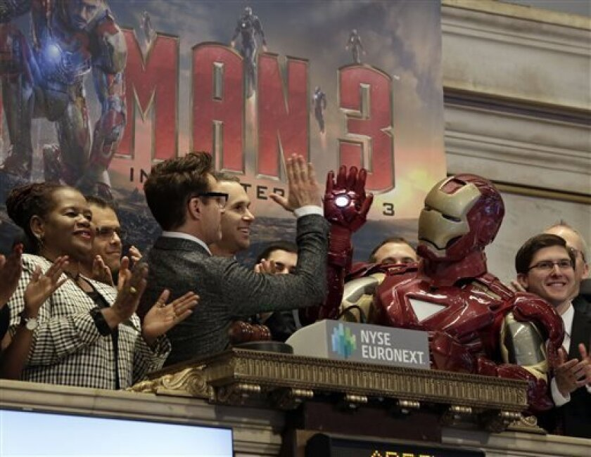 """Actor Robert Downey Jr. gives a high-five to his """"Iron Man"""" character during opening bell ceremonies of the New York Stock Exchange, Tuesday, April 30, 2013. Stock prices are opening mostly lower on Wall Street as weak earnings from Pfizer and other companies drag down major market averages. Downey's film, """"Iron Man 3,"""" also starring Don Cheadle and Gwyneth Paltrow, opens nationwide on May 3. (AP Photo/Richard Drew)"""