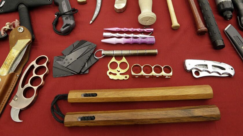 Nunchucks, bottom, are shown in 2017 at Seattle-Tacoma International Airport among objects confiscated from carry-on luggage. A federal court says New York's ban on the weapon made famous by Bruce Lee is unconstitutional.
