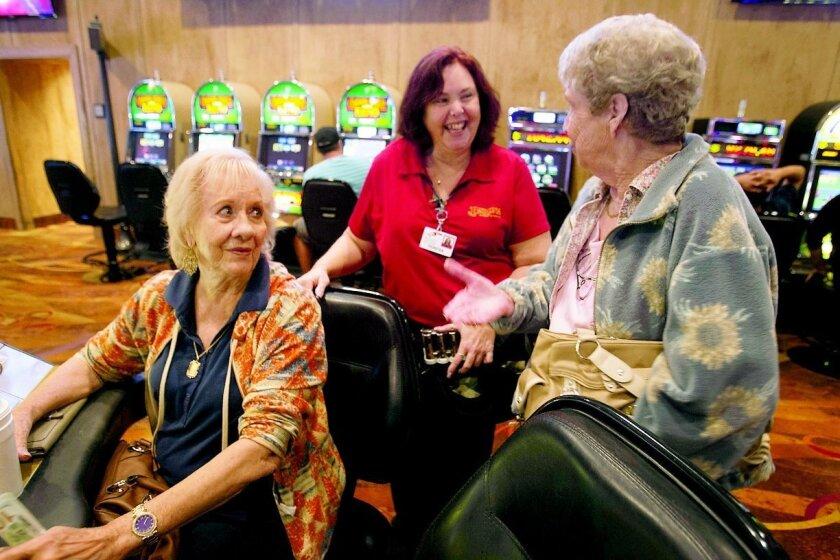From left, guest Billie Lee, floor cashier Teresa Varnadore and guest Bonnie Taramasco talk at Barona Casino. Varnadore has worked at Barona for 16 years. JOHN GIBBINS • U-T photos
