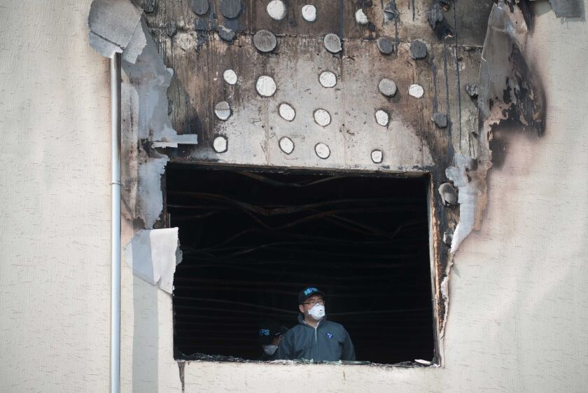 An investigator stands in a window of the fire-damaged Hyosarang nursing home near Janseong.