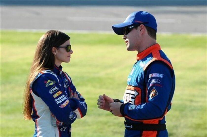 FILE - In this Nov. 3, 2012, file photo, drivers Danica Patrick, left, talks with Ricky Stenhouse Jr., as they wait on pit road during qualifying for a NASCAR Nationwide series auto race at Texas Motor Speedway in Fort Worth, Texas. Patrick slid into her chair at NASCAR media day Thursday, Feb. 14,