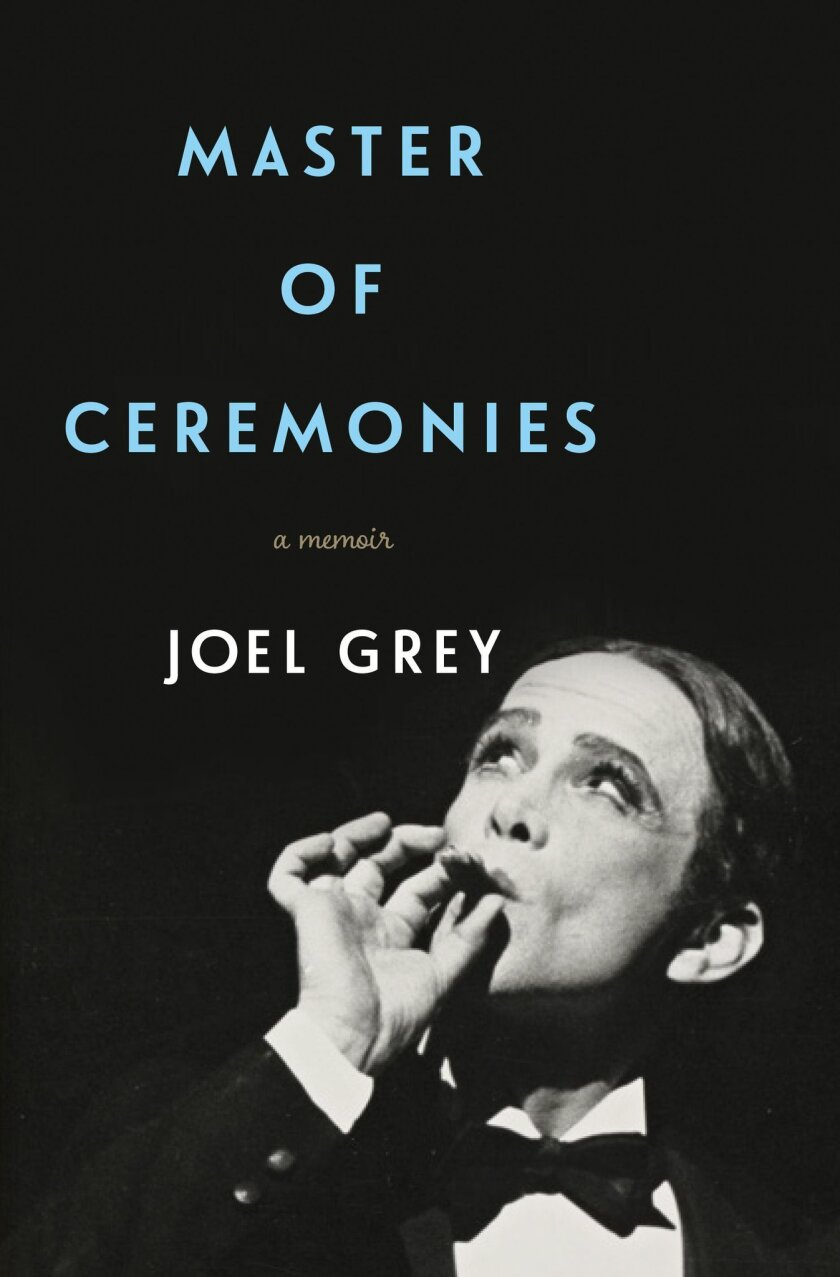 """This book cover image released by Flatiron Books shows """"Master of Ceremonies,"""" a memoir by Joel Grey. The memoir traces his childhood in Cleveland, his rise as a nightclub performer and his breakthrough both on stage and film as the creepy Emcee with whitened face, rouged cheeks and cupid's-bow lip"""