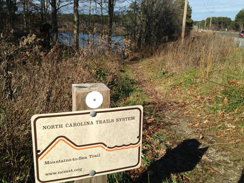 In this Thursday, Dec. 18, 2014 photo, a sign marking a trail head for the Mountains-to-Sea trail is seen near Falls Lake in Wake Forest, N.C.  Efforts to boost the 1,000-mile trail in 2015 include a master plan commissioned by North Carolina, a comprehensive hiking guide and trail additions in sev