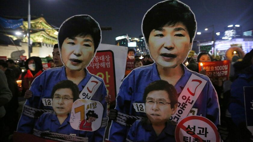 Protesters hold cutouts of impeached President Park Geun-hye, top, as they march toward the presidential house during a candlelight vigil in Seoul on Jan. 7, 2017.