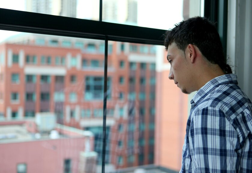 In this Saturday, July 26, 2014, photo, Celvyn Mejia Romero looks out an office window before an interview at the Greater Boston Legal Services in Boston. Romero is still fighting to stay in America. His tenacious and unusually long bid for asylum offers a singular glimpse into the complex world of immigration law and rules that many legal experts say are fiendishly difficult for anyone, especially kids, to negotiate. And yet at 22, Mejia Romero, who has lived longer in the U.S. than in his native Honduras, is hoping he'll prevail. (AP Photo/Mary Schwalm)