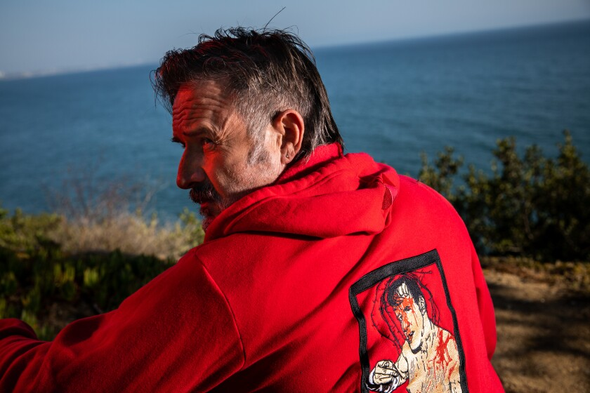 """David Arquette wears a custom sweatshirt by Stitch Kings depicting an image of himself from his 2018 wrestling """"deathmatch."""""""