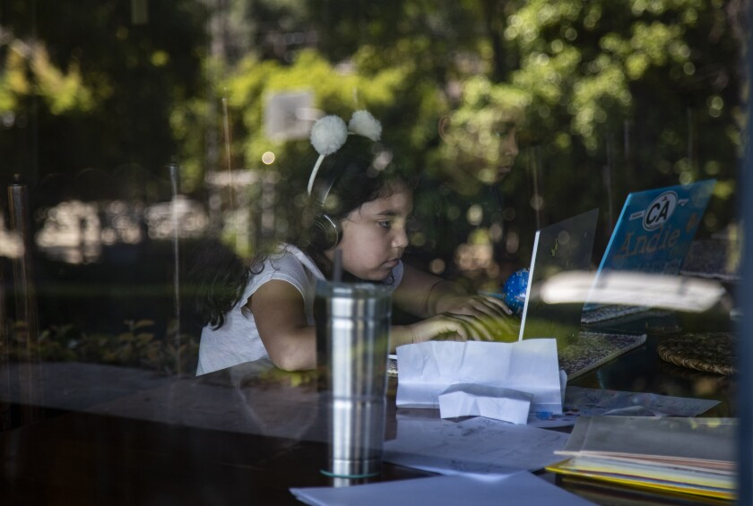 Rosie Roth, left, and Andie Bristow sit at a dining room table for typing class during home school in the midst of the coronavirus pandemic on April 21 in Riverside.