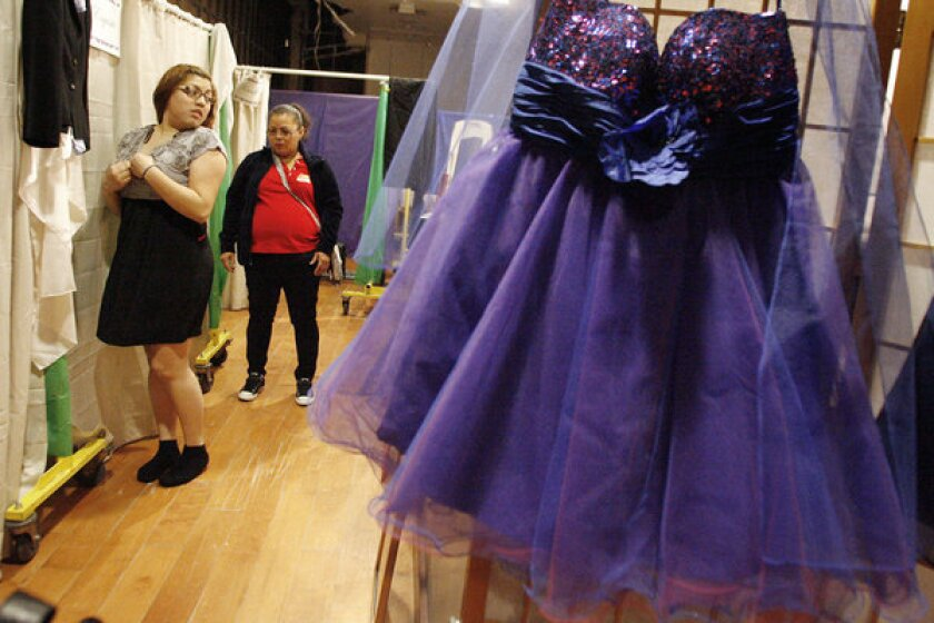 Maria Gamez, right, looks at her daughter, Amy, 19, while she tries on prom dresses during Renal Support Network's makeover day, which took place at the Glendale Galleria.