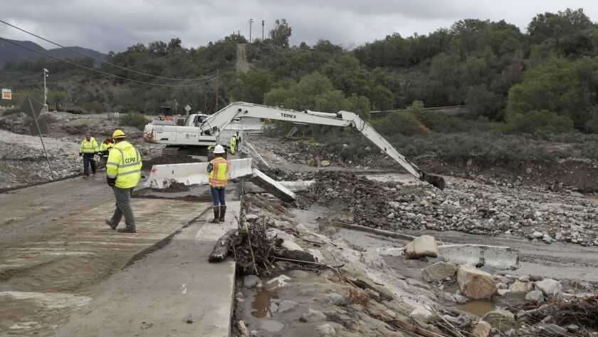 Crews use an excavator to remove large boulders and debris that were swept down Trabuco Creek from recent downpours on the Trabuco Canyon Road bridge earlier this month. Forecasters predict the Holy fire burn scar could see 2.5 to 6 inches of rain later this week.