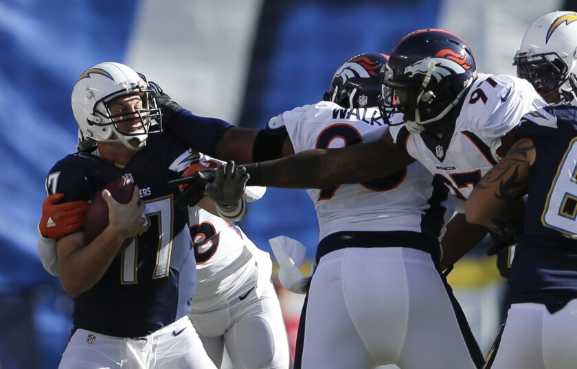 San Diego Chargers quarterback Philip Rivers, let, is sacked by the Denver Broncos defence during the first half in an NFL football game Sunday, Dec. 6, 2015, in San Diego. (AP Photo/Gregory Bull)