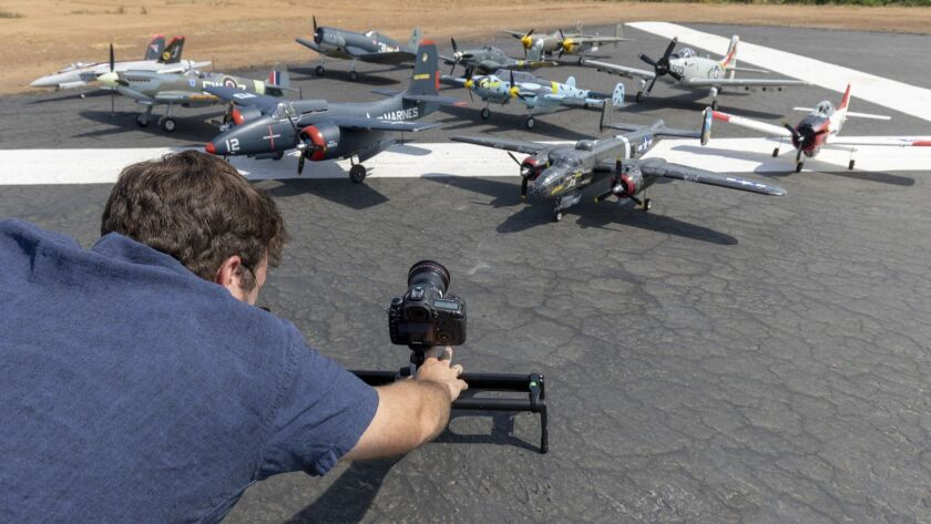 Photographer Elliott Cook takes video of model airplanes for a UK documentary production company that is doing a project having to do with angled flight decks found on aircraft carriers. The production took place at the Palomar R/C Flying Club's model airplane field in Fallbrook.
