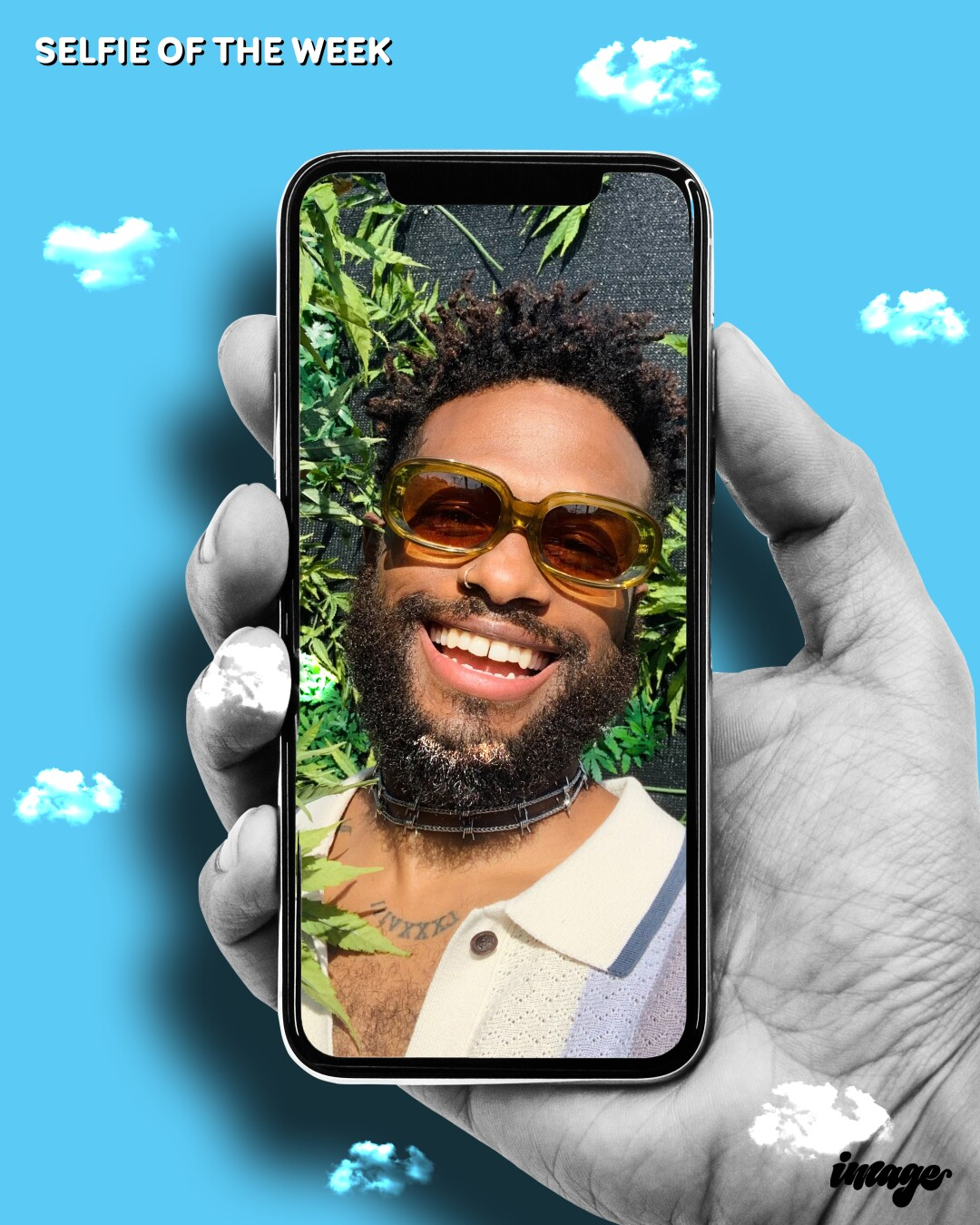 A hand holds a cellphone displaying a selfie of a smiling, bearded Black man in sunglasses.