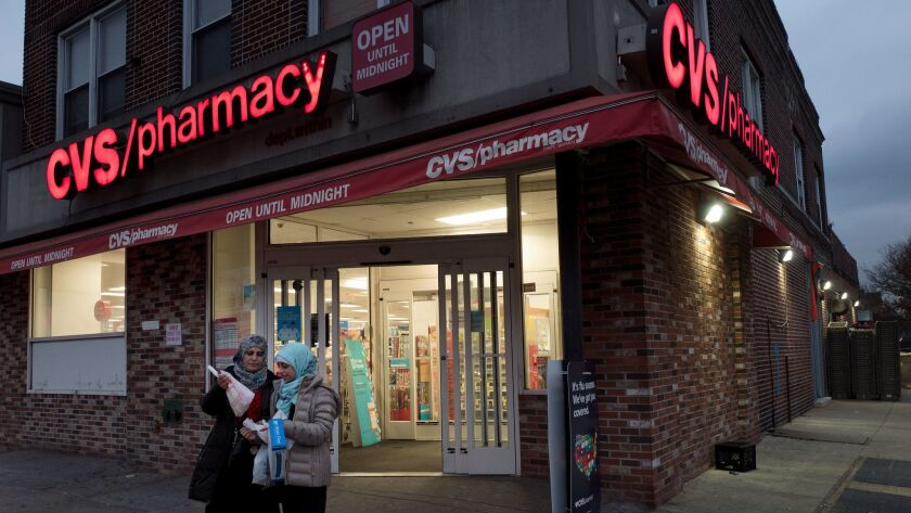 Customers leave a CVS Pharmacy, Sunday, Dec. 3, 2017 in the Brooklyn borough of New York. CVS will b