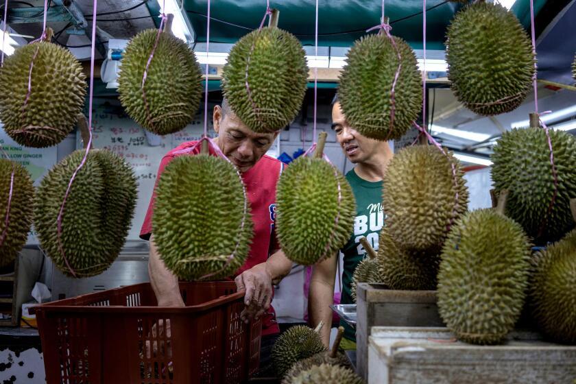 Un cliente, vestido con una camisa verde, pide 'durians' en un puesto de carretera durante el Festival de Durian en Georgetown, Malasia.