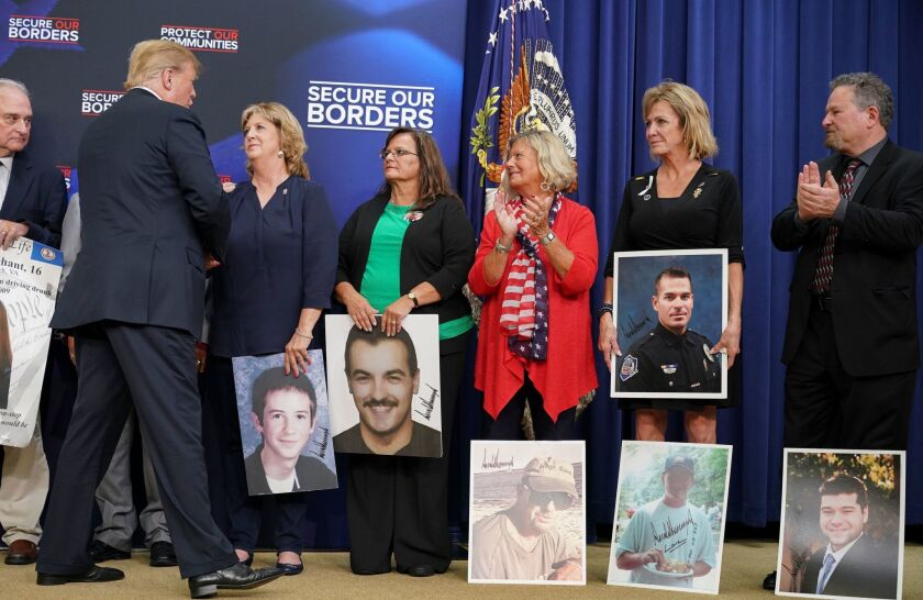 President Trump greets people holding posters of people allegedly killed by illegal immigrants before speaking on immigration at the White House on Friday.