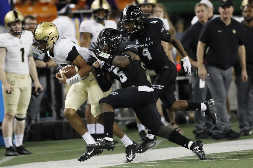 Army quarterback Christian Anderson (13) gets shoved out of bounds by Hawaii defensive back Khoury Bethley (5) during the second half of an NCAA college football game Saturday, Nov. 30, 2019 in Honolulu. (AP Photo/Marco Garcia)