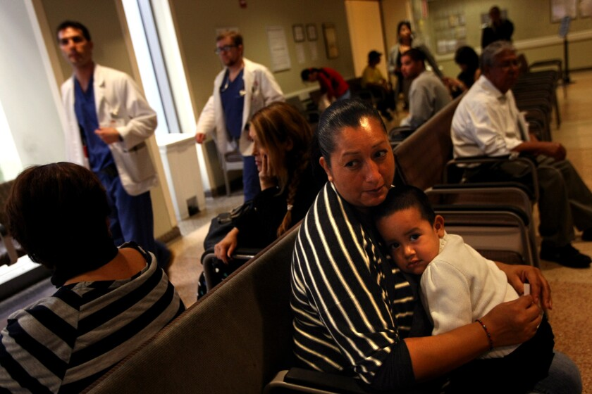 A Medi-Cal patient and her son wait to see a doctor in the emergency ward of L.A. County-USC Medical Center in Los Angeles in 2013. An audit released Tuesday found that California hasn't ensured patients who are part of Medi-Cal have adequate access to doctors.
