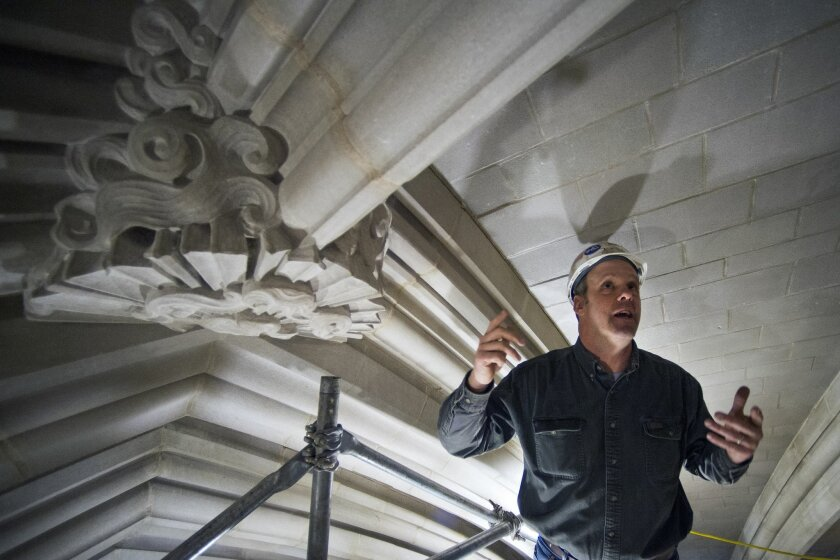 Head Mason Joe Alonso stands next to a boss stone in the ceiling 100 feet above the nave floor of the Washington National Cathedral in Washington, Wednesday, Feb. 18, 2015, as he talks about repairs and cleaning of the stonework at cathedral, The Washington National Cathedral has finished the first