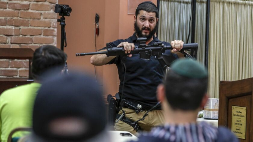 LOS ANGELES, CA, WEDNESDAY, MAY 8, 2019 -- Raziel Cohen holds an AR-15 rifle while delivering infor