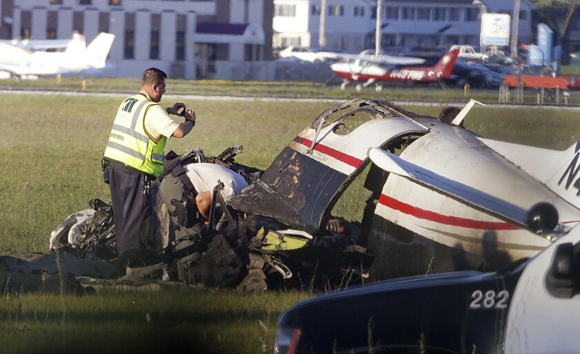 Milwaukee County firefighters and law enforcement officers respond to a crash site of a small plane which caught fire Wednesday, July 29, 2015, at Timmerman Airport in Milwaukee. Milwaukee County Department of Transportation Director Brian Dranzik said in a statement the accident happened around 6:15 p.m. Wednesday at the airport on the city's northwest side. (Rick Wood/Milwaukee Journal-Sentinel via AP)