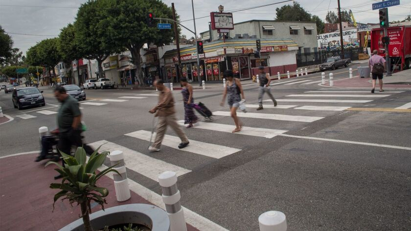 Pedestrians cross the street in an East L.A. crosswalk where the curbs have been extended.