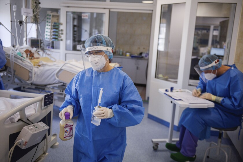 A health worker carries medication inside the Intensive Care Unit at the hospital in Bochnia, Poland, Monday March 26, 2021. Polish hospitals struggled over the Easter weekend with a massive number of people infected with COVID-19 following a huge surge in infections across Central and Eastern Europe in recent weeks. Tougher new pandemic restrictions were ordered in Poland for a two-week period surrounding Easter in order to slow down the infection rate. (AP Photo/Omar Marques)