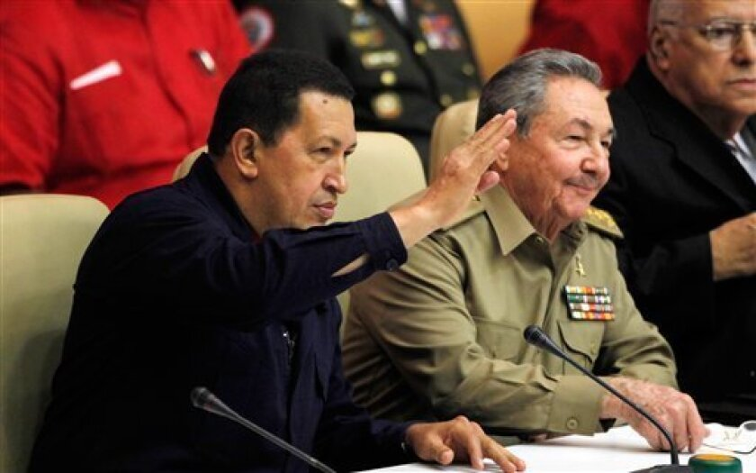 Venezuela's President Hugo Chavez, left, waves to the crowd next to Cuba's President Raul Castro during a meeting in Havana, Cuba, Monday Nov. 8, 2010. Chavez is in Cuba to attend meetings between the two governments in the tenth anniversary of their aid and commercial agreements. (AP Photo/Javier Galeano)